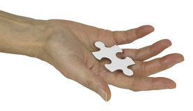 The Missing Piece of the Jigsaw. Female hand holding a piece of jigsaw isolated on a white background Royalty Free Stock Photo
