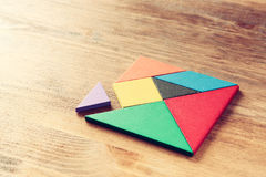 A missing piece in a square tangram puzzle, over wooden table. Royalty Free Stock Photos