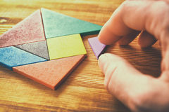 A missing piece in a square tangram puzzle, over wooden table. Stock Images