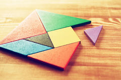 A missing piece in a square tangram puzzle, over wooden table. Royalty Free Stock Photo