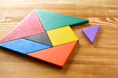 A missing piece in a square tangram puzzle, over wooden table. Royalty Free Stock Images
