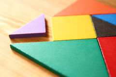 A missing piece in a square tangram puzzle, over wooden table. Royalty Free Stock Image