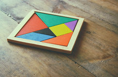 A missing piece in a square tangram puzzle, over wooden table. Royalty Free Stock Photography