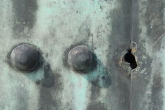 Missing rivet. One missing rivet in a row of three on weathered rusty metal plate Royalty Free Stock Photos