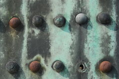 Missing rivet. One missing rivet in two rows of five each on weathered rusty metal plate Stock Images