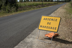 Missing road markings. Medoc Bordeaux France - August 2016 - Roadside sign advising motorists thet there are no road markings Royalty Free Stock Photos