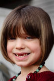 Missing Teeth Smile. A closeup of a dark haired, blue eyes little girl with a big smile showing two missing front teeth. Shallow depth of field Stock Photography