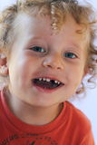 Missing tooth. A closeup of a cute 2 year old toddler with curly blond ringlets missing a tooth. Shallow DOF Stock Photo