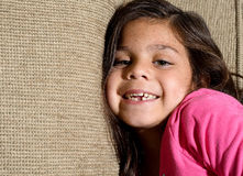 Missing a tooth. A little girl sitting on the couch smiling showing that she's missing her first tooth Stock Photo