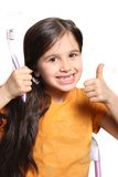 Missing two front teeth. Little seven year old girl shows big smile showing missing top front teeth and holding a toothbrush and thumbs up on a white background Royalty Free Stock Photos