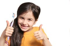 Missing two front teeth. Little seven year old girl shows big smile showing missing top front teeth and holding a toothbrush with thumbs up on a white background Royalty Free Stock Photo