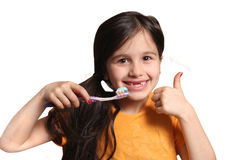 Missing two front teeth. Little seven year old girl shows big smile showing missing top front teeth and holding a toothbrush with toothpaste and thumbs up on a Stock Photo