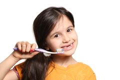 Missing two front teeth. Little seven year old girl shows big smile showing missing top front teeth and holding a toothbrush on a white background Royalty Free Stock Image