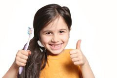 Missing two front teeth. Little seven year old girl shows big smile showing missing top front teeth and holding a toothbrush on a white background Stock Image