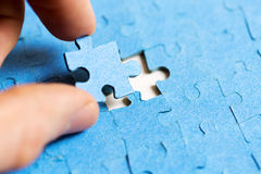 Mission complete concept - hand placing last piece of puz. Mission complete concept - hand placing last piece of jigsaw puzzle royalty free stock photo