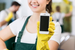 Mission complete, house is clean!. Smiling charwoman in uniform holding cellphone stock photo