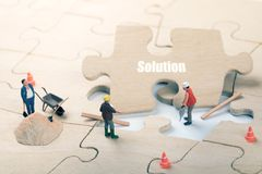 Mission complete and problem solution concept. Construction worker figurines on jigsaw puzzle stock images