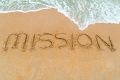 MISSION inscription written on sandy beach with wave approaching Royalty Free Stock Images