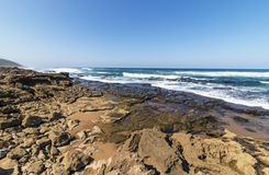 Mission Rocks Beach in Isimangaliso Wetland Park South Africa. Rocks sand ocean and blue coastal skyline at Mission Rocks beach near Cape Vidal in Isimangaliso royalty free stock image