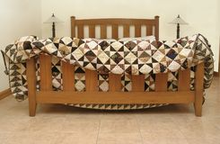 Mission-style bed with handmade quilt stock photos