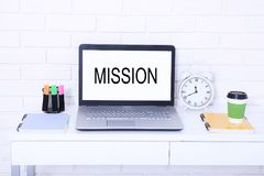 Missione di parola Testo sul monitor Posto di lavoro con il computer, la tazza di caffè e l'orologio Derisione alta e spazio dell Fotografia Stock Libera da Diritti