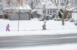 Mississauga, Καναδάς - 12 Δεκεμβρίου 2017: Οικογένεια που περπατά στο σχολείο στο χιονώδη καιρό Στοκ Φωτογραφία