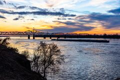Free Mississippi River Bridge And Towboat With Barges At Sunset In Vicksburg, MS Royalty Free Stock Photo - 182188045