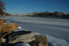 Mississippi River Frozen. Mississippi River at Minneapolis frozen with railroad tressle in background royalty free stock photo