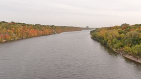 Mississippi River taken from bridge between Minneapolis and St. Paul - fall colors on trees - green, yellow, orange, red.  royalty free stock image