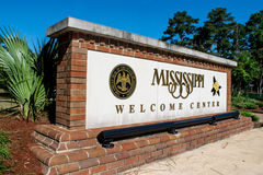 Mississippi, USA, Welcome Center Sign (editorial). Welcome Center to state of Mississippi in southern USA. The white sign is surrounded by brickwork. Trees in royalty free stock image