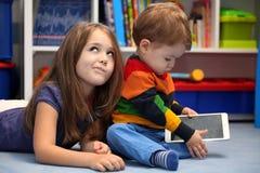 Misslyckad flicka med hennes lilla broder som använder en minnestavlacomput Royaltyfri Fotografi