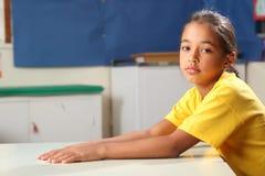 Missmutiges Schulmädchen 10, das an ihrem Klassenzimmerschreibtisch wartet Lizenzfreies Stockbild