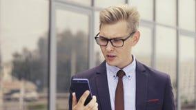 Missnöjd affärsman som har otrevlig online-video pratstund Man som uttrycker hans retning Ilsken man som anv?nder Smartphone lager videofilmer