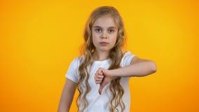 Missnöjd gullig flicka som visar tummar-ner, motviljaservice, fattigt kvalitets- gods lager videofilmer