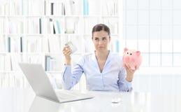 Missnöjd kvinna på datoren med kreditkorten och spargrisen fotografering för bildbyråer
