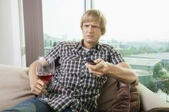 Missnöjd mitt--vuxen människa man med hållande ögonen på television för vinexponeringsglas på soffan hemma Fotografering för Bildbyråer