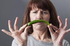 Missnöjd 50-talkvinna som äcklas på idén av att äta chili- eller kryddaingredienser Royaltyfri Foto