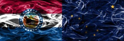 Missouri gegen Konzept-Rauchflaggen Alaskas die bunten nebeneinander gesetzt lizenzfreies stockfoto