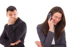 Misstänksam man som ser hans kvinna som talar på telefonen royaltyfria foton