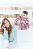 Misstänksam man som ser hans kvinna som talar på telefonen arkivfoton