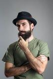 Misstänksam skeptisk man som trycker på hans skägg som ser kameran fotografering för bildbyråer