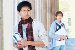Misstänksamma asiatiska studenter utomhus Royaltyfria Bilder