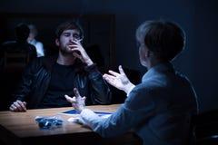 Misstänkt man som röker en cigarett Arkivfoto