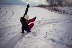 Misstap op het gladde ijs en de sneeuw op het wegspoor bij het land in het bevriezen van de winterdag stock fotografie