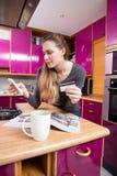 Misstrauische junge Frau, die ihren Handy für E-Commerce verwendet stockbild