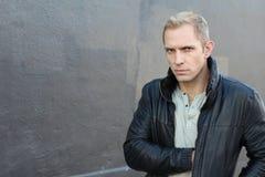 Misstrauischer blonder Mann, der etwas seine Lederjacke herauszieht Stockfoto