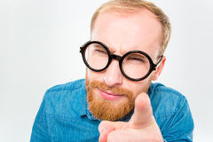 Misstrauischer bärtiger Mann in den lustigen runden Gläsern zeigend auf Sie Lizenzfreie Stockfotos