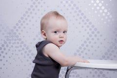 Misstrauischer Säuglingsjunge lehnt sich auf dem weißen Stuhl Stockfotos
