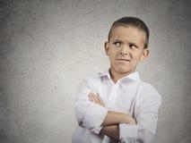 Misstrauischer, vorsichtiger Kinderjunge, der mit Ungläubigkeit schaut Stockbilder
