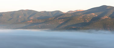Mist in bergvallei stock afbeeldingen
